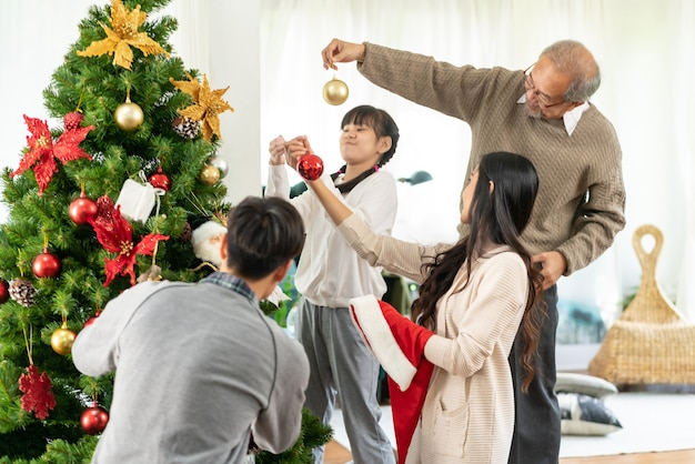装飾品でクリスマスツリーを飾る小さなアジアの女の子にクローズアップ