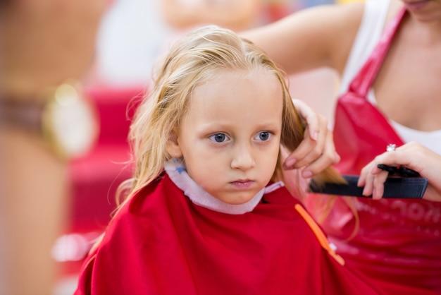 뷰티 살롱에서 그녀의 헤어 스타일을 변경하는 어린 소녀에 가까이