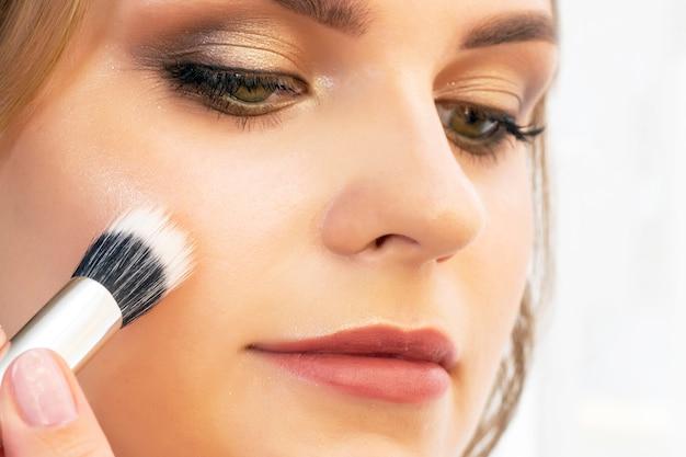 さまざまな美容製品をモデルに適用するメイクアップアーティストのクローズアップ