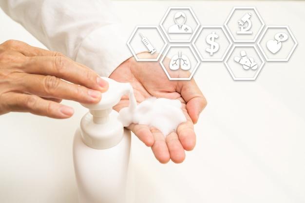 液体石鹸をポンピングする男の手にクローズアップ。