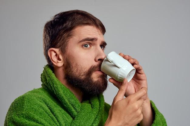 カップから飲む緑のローブで男にクローズアップ
