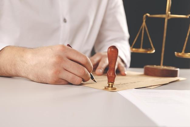 Закройте вверх на человека нотариуса государственной руки чернилами штамповки документа. нотариальная общественная концепция