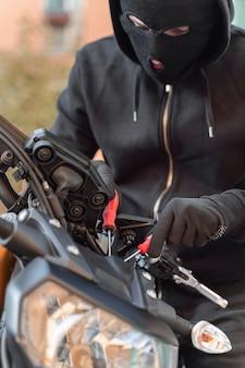 Крупным планом мужчина готовится украсть мотоцикл