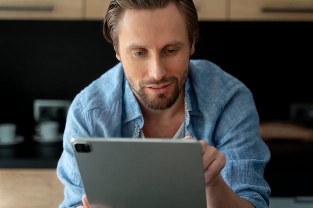 Крупным планом на человека, использующего цифровое устройство дома