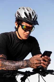 전기 자전거를 타고 있는 동안 전화를 사용하는 남자에게 클로즈업