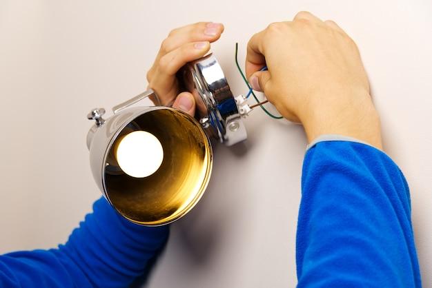 Закройте человека, проводящего провода лампы на стене