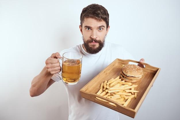 ジャンクフードとビールのトレイを持つ男にクローズアップ