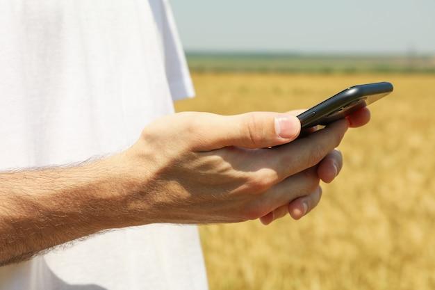 麦畑で電話を持つ男にクローズアップ