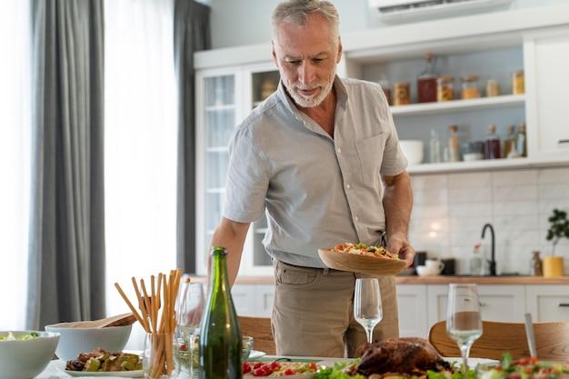 家族のために夕食を準備している成熟した男性にクローズアップ