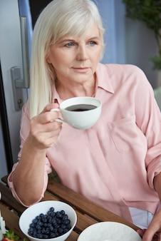 バルコニーでおいしいコーヒーを楽しんでいる成熟した女性にクローズアップ