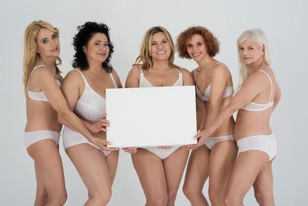 下着の空のホワイトボードで成熟した女性にクローズアップ