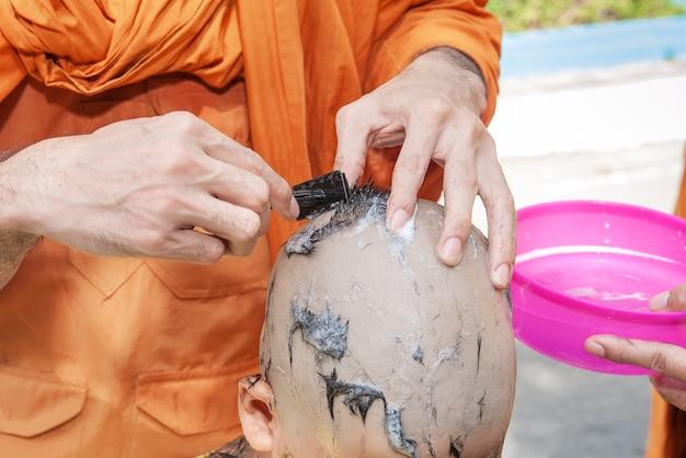 Крупным планом монаха, использующего руки, чтобы побрить мальчика