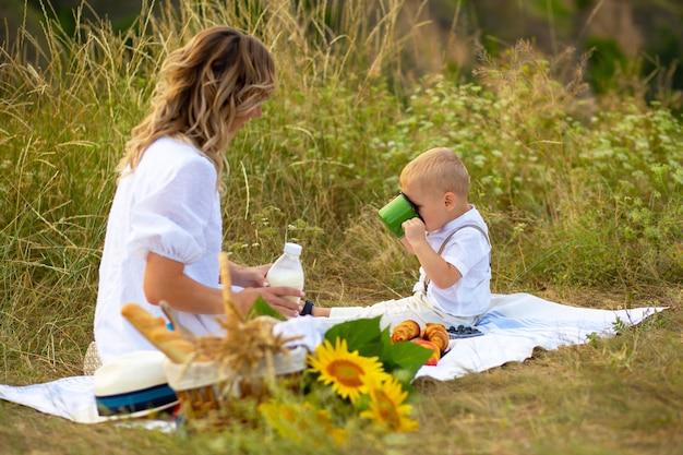 自然の中で彼女の息子とのピクニックを持つ母親にクローズアップ
