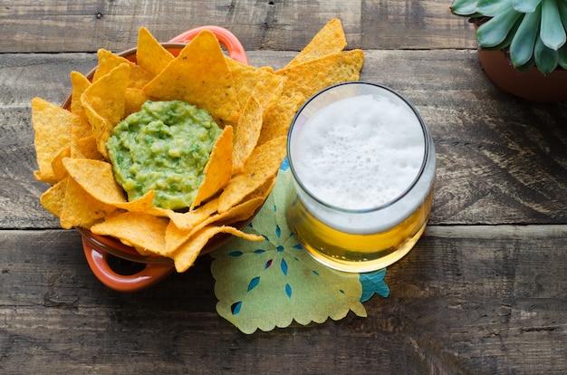 Крупным планом начо с гуакамоле и пивом