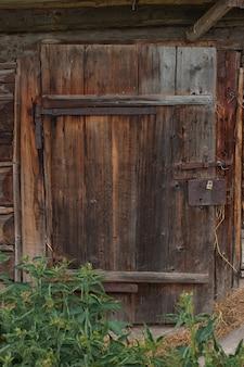 古い風化した木造の納屋のドアにクローズアップ