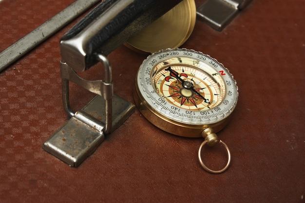 Крупным планом на старый старый чемодан и компас изолированные