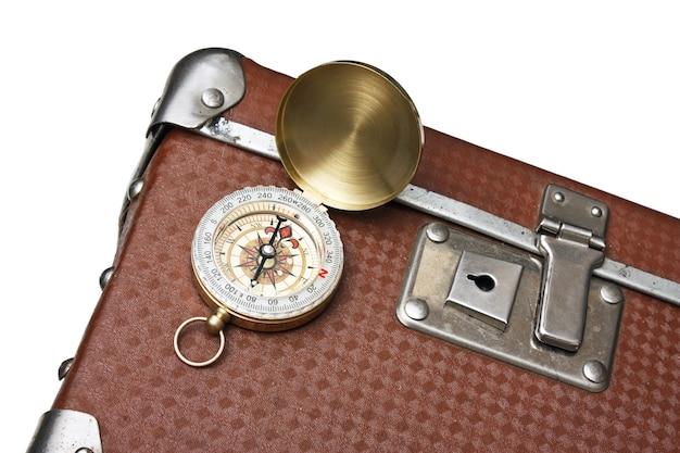 Крупным планом на старый чемодан и компас изолированные