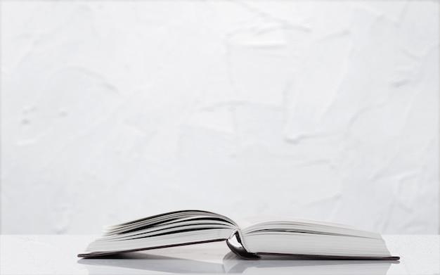 隔離されたテーブルの開いた本をクローズアップ