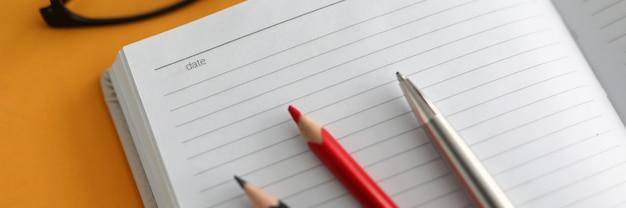 Крупный план, на открытом дневнике лежат цветные карандаши и ручка