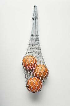 Крупным планом апельсины в эко авоське