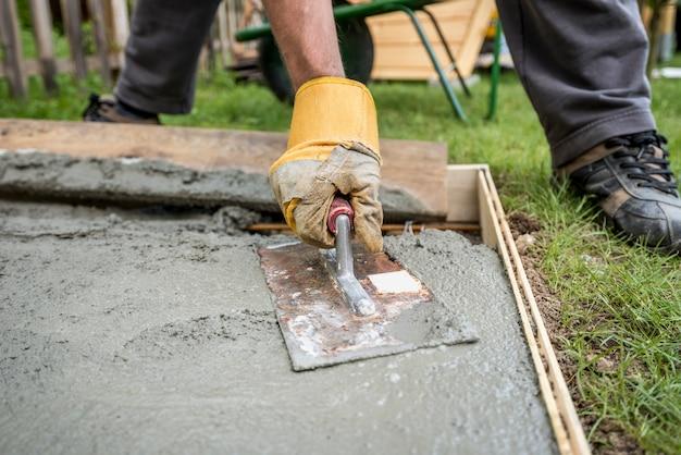 Крупным планом на асфальтоукладчик разглаживания свежего бетона