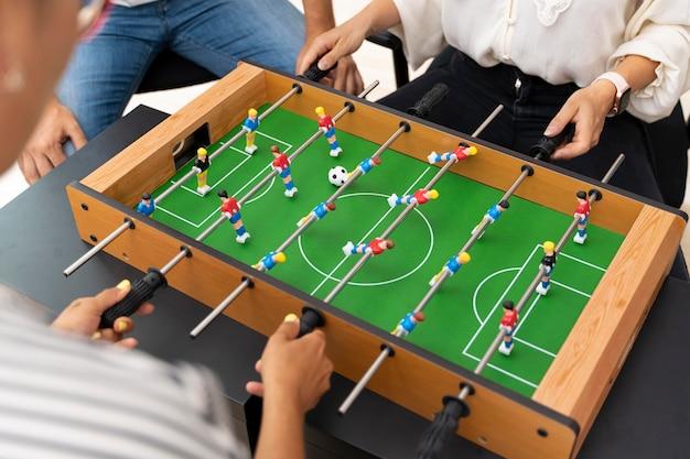 テーブルサッカーをしながら楽しんでいる人々にクローズアップ