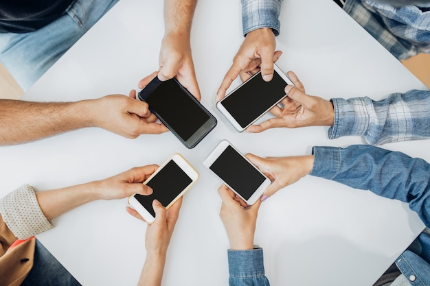 テーブルでスマートフォンを使用している人にクローズアップ