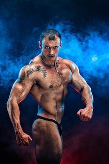 완벽한 복근을 닫습니다. 완벽한 복근, 어깨, 팔뚝, 삼두근 및 가슴을 가진 강력한 보디 빌더, 파란색, 빨간색 연기로 근육을 구부리는 개인 피트니스 트레이너