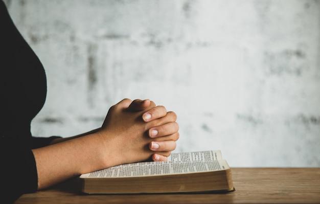 聖書の近くで祈っている人にクローズアップ