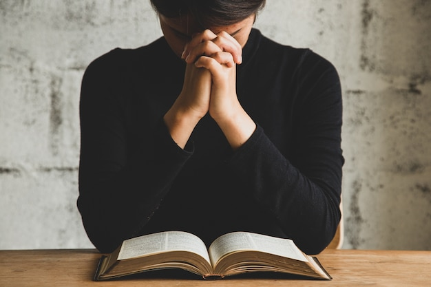 Крупным планом человека, молящегося возле библии