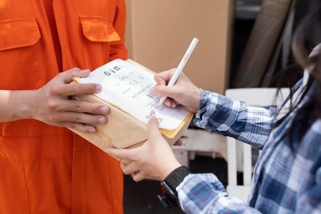 小包配達に署名する人のクローズアップ