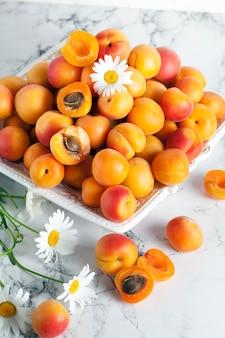 Крупным планом на кучу спелых абрикосов с ромашками
