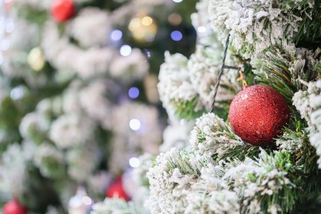 빨간 공을 크리스마스 나무에 걸어 닫습니다