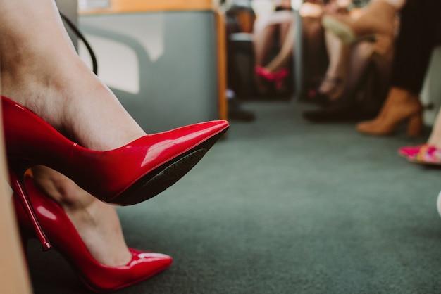 Крупным планом на красных каблуках девушки идут на вечеринку