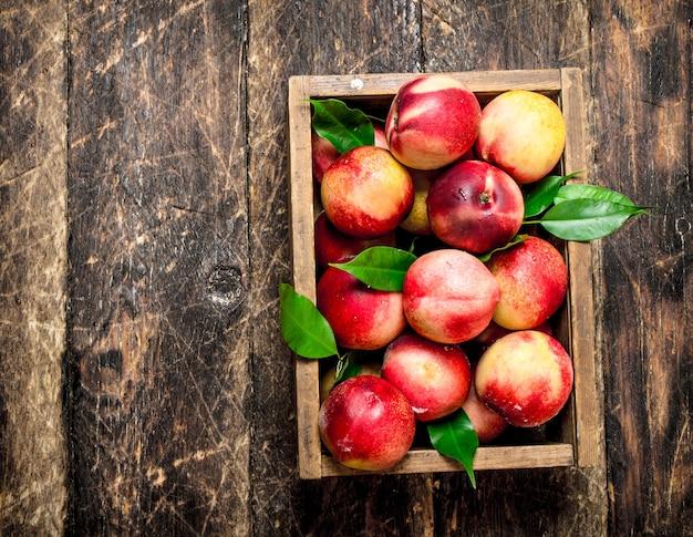 Крупным планом спелые персики в коробке