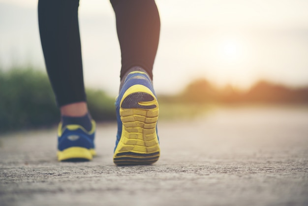 ランニングシューズを閉じてフィットネス女性のトレーニングとジョギング