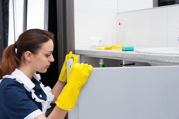 青いドレスと白いエプロンのオープニングキャビネットを身に着けた一人の女性の家事労働者をクローズアップします。彼女の手には黄色の手袋があり、流しの上にはスポンジがあります。