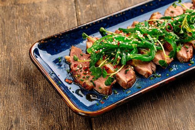 木製の背景に海藻チュカとスライスした乾燥熟成ロースト鴨胸肉のクローズアップ