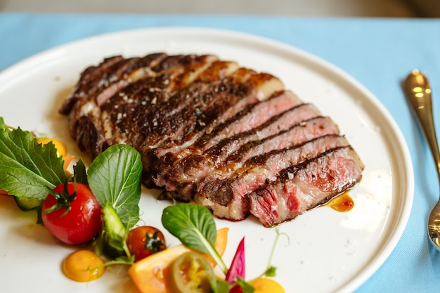 青いテーブルの上に新鮮な野菜のサラダとスライスしたリブアイビーフステーキのクローズアップ