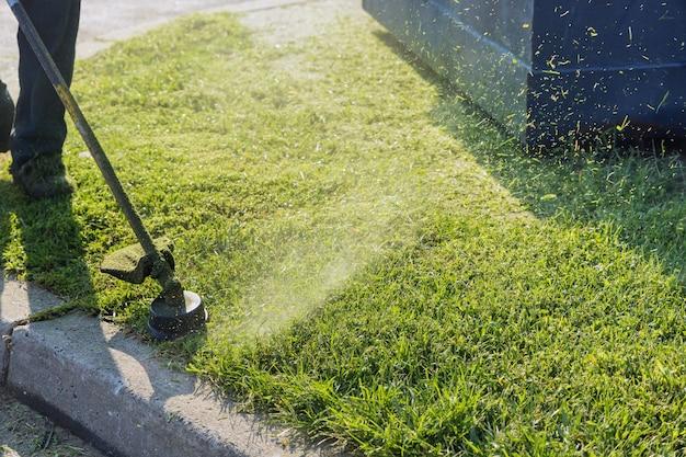 정원에서 잔디를 자르는 마당에서 일하는 스트링 트리머 헤드 잡초 커터 브러시 커터에 가까이