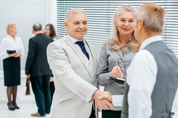 オフィスで握手する成功したビジネスマンにクローズアップ