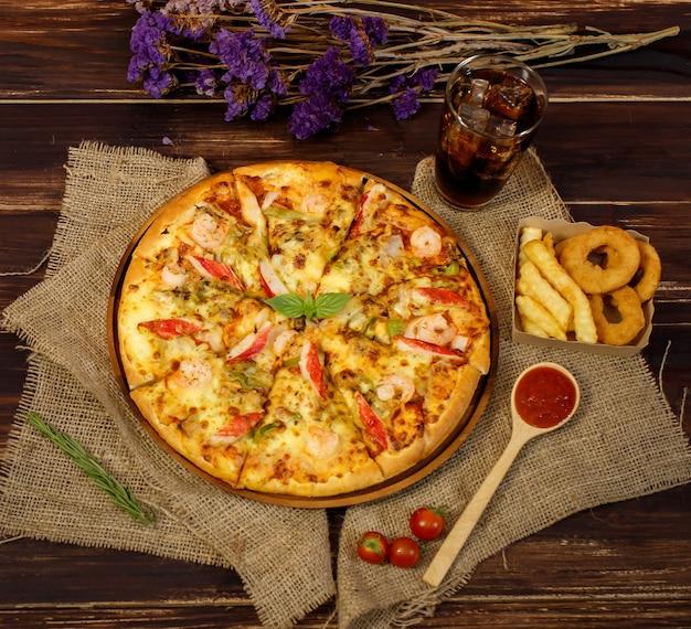 마른 보라색 꽃, 차가운 음료, 튀긴 양파, 감자, 토마토, 케첩을 나무 테이블에 얹은 자루천에 맛있는 홈메이드 해산물 피자를 올려보세요. 음식과 음료 개념입니다.