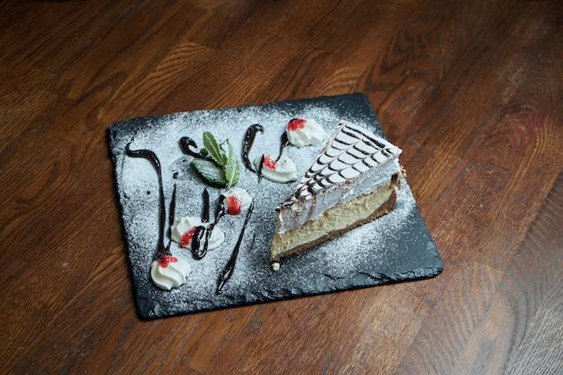 の繊細な風通しの良いチーズケーキのおいしいスライスにクローズアップ。夕食後に美味しいデザートケーキ。