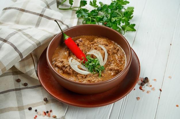 Закройте на вкусный, традиционный суп харчо с говядиной, рисом, пюре из чернослива и нарезанные грецкие орехи в керамической миске на деревянных фоне. вкусная грузинская кухня