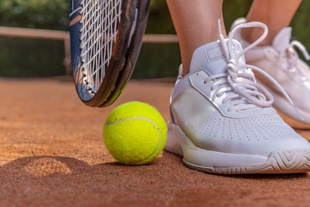 コート、ラケット、ボール、靴のテニスプレーヤーのクローズアップ