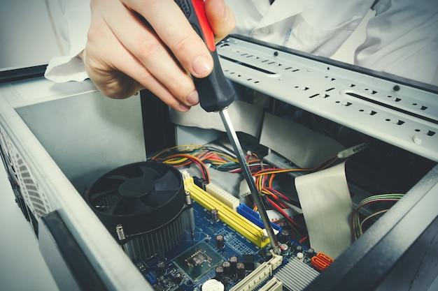 Pc 컴퓨터를 수리하는 기술자의 드라이버 도구로 손을 클로즈업.
