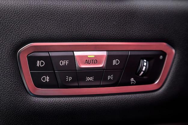 車のドアにクロームフレーム、一般的な黒の本革、自動調整レベルダッシュボードを備えたヘッドライトスイッチコントロールボタンのクローズアップ。高級車のインテリア:部品、ボタン、ノブ