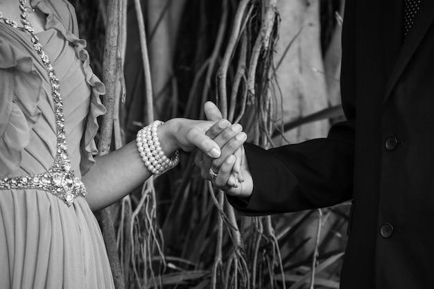 木の枝と根と公園で手をつないでいる結婚式のカップルのクローズアップ