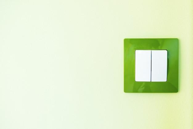 コピースペースのある緑の壁の白色光スイッチをクローズアップ