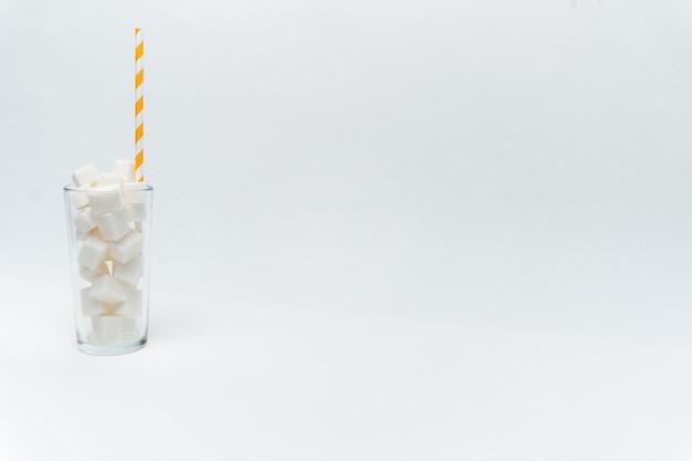 ストローでグラスに白い砂糖の立方体をクローズアップ
